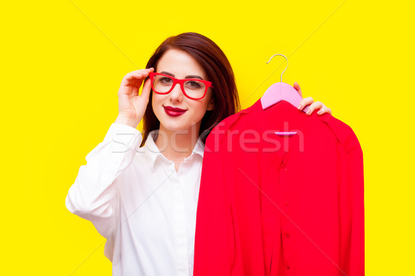 beautiful young woman with shirt on hanger standing in front of  Stock photo © Massonforstock