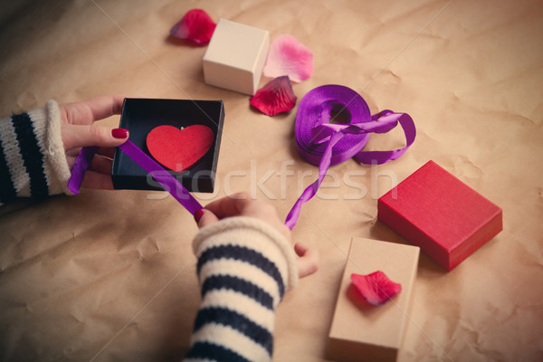 white caucasian hands wrapping heart shaped toy in box on the wo Stock photo © Massonforstock