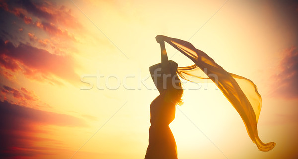 photo of beautiful young woman with shawl on the wonderful sunse Stock photo © Massonforstock