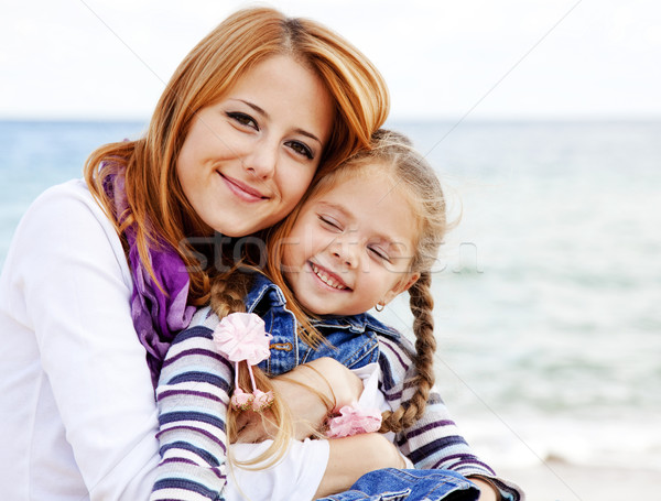 Two sisters 5 and 22 years old at the beach in sunny autumn day. Stock photo © Massonforstock