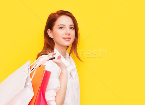 Nő bevásárlótáskák portré vörös hajú nő citromsárga munka Stock fotó © Massonforstock