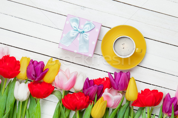 photo of cup of coffee, cute gift and colorful tulips on the won Stock photo © Massonforstock