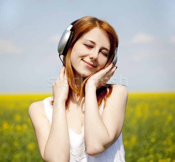 Girl with headphone at rapeseed field. Stock photo © Massonforstock