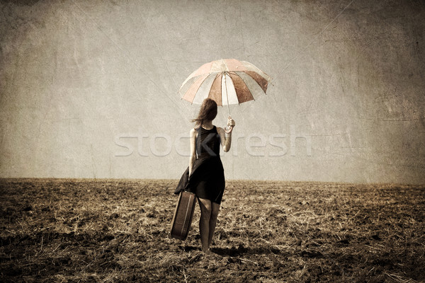 Redhead girl with umbrella and suitcase at windy grass meadow. Stock photo © Massonforstock