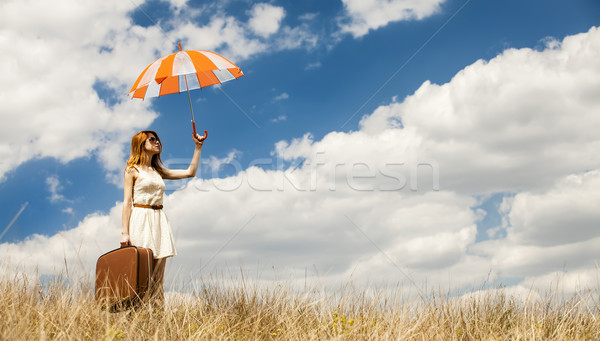 Beautiful redhead girl with umbrella and suitcase at outdoor. Stock photo © Massonforstock