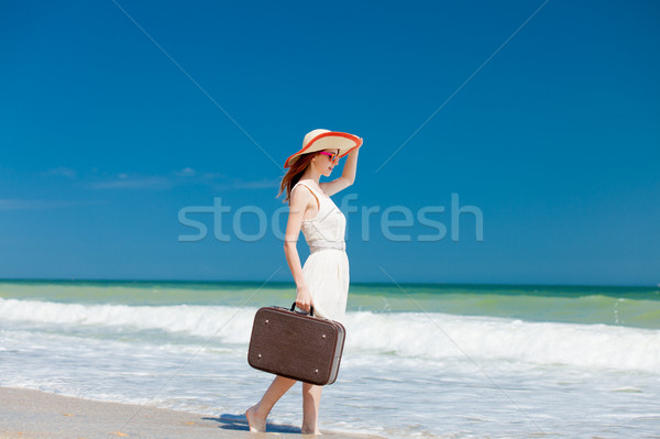 photo of beautiful young woman standing with suitcase on the won Stock photo © Massonforstock