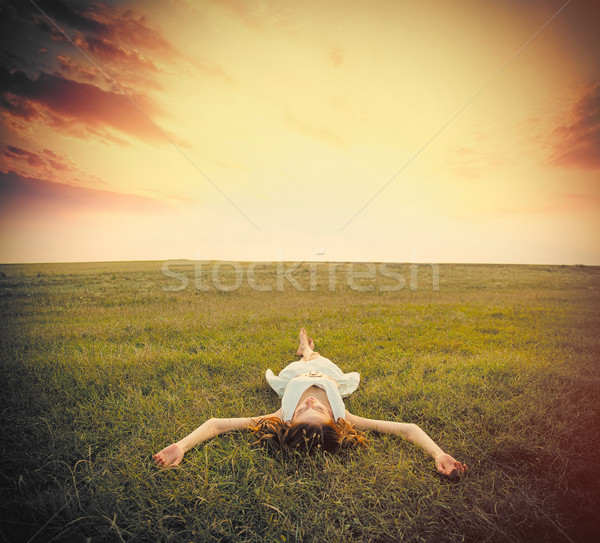 photo of beautiful young woman lying in the field on the sky bac Stock photo © Massonforstock