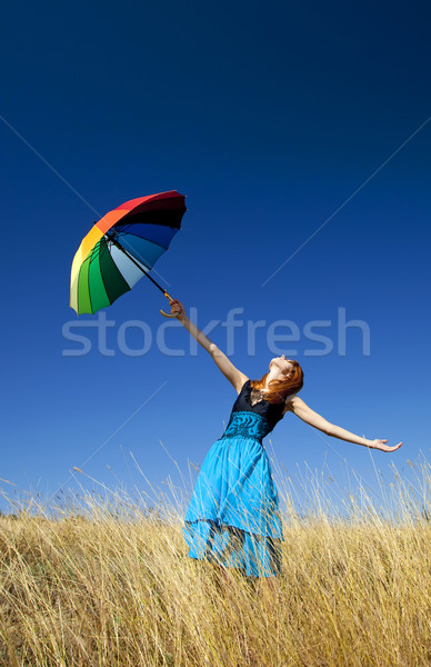 Redhead girl with umbrella at windy grass meadow. Stock photo © Massonforstock
