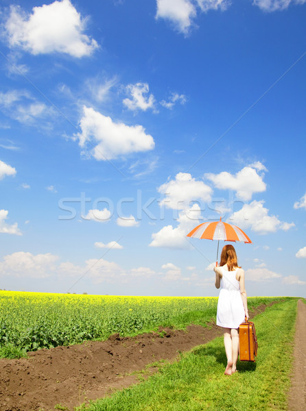 Redhead enchantress walking near rapeseed field. Stock photo © Massonforstock