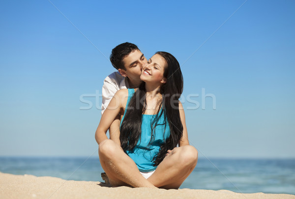 Beautiful couple kissing on the beach. Stock photo © Massonforstock