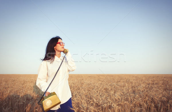 Young brunette girl with green dial handset Stock photo © Massonforstock