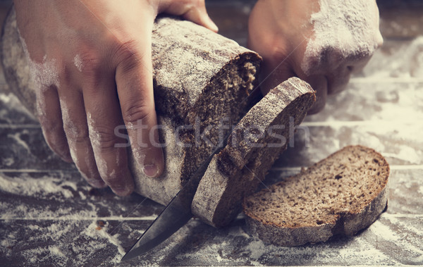 Male hands slicing home-made bread Stock photo © Massonforstock