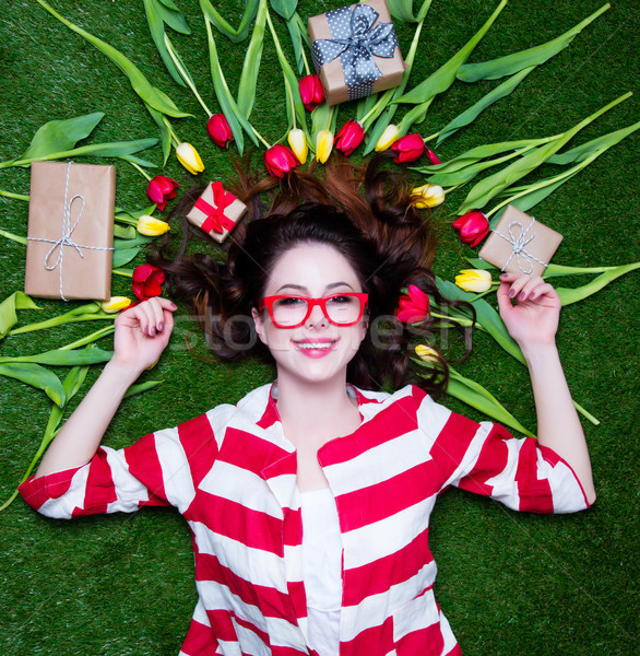 Stock photo: Portrait of a young styled redhead woman with tulips around and