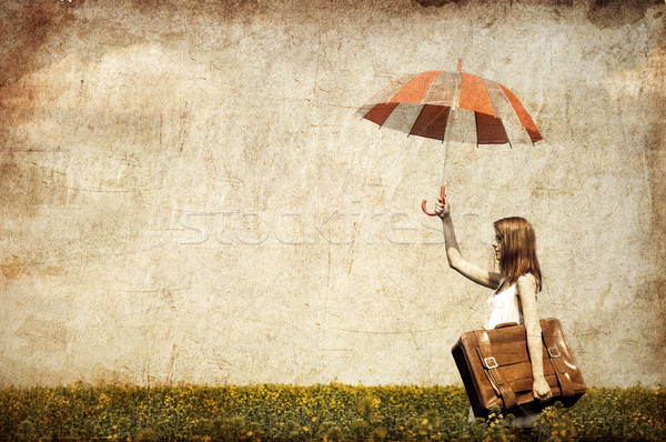 Redhead enchantress with umbrella and suitcase Stock photo © Massonforstock