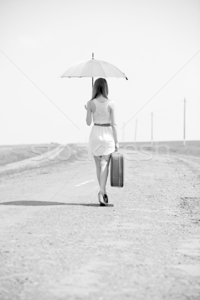Lonely girl with suitcase and umrella at country road. Stock photo © Massonforstock