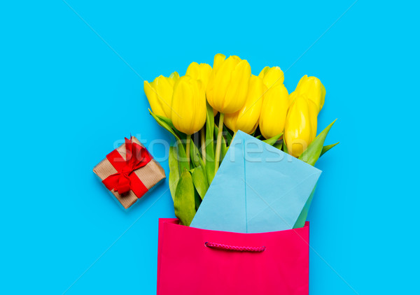 bunch of yellow tulips and blue envelope in cool shopping bag an Stock photo © Massonforstock