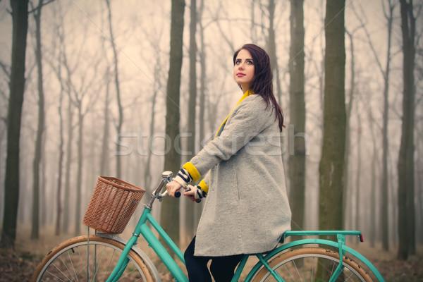 Gyönyörű fiatal nő ül bicikli csodálatos erdő Stock fotó © Massonforstock