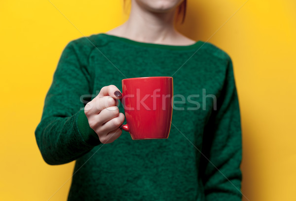 beautiful young woman hand holding a red cup of the wonderful ye Stock photo © Massonforstock