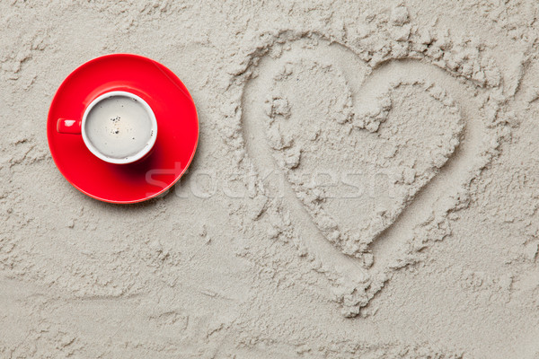 photo of heart shaped drawing and cup of coffee on the sand on t Stock photo © Massonforstock