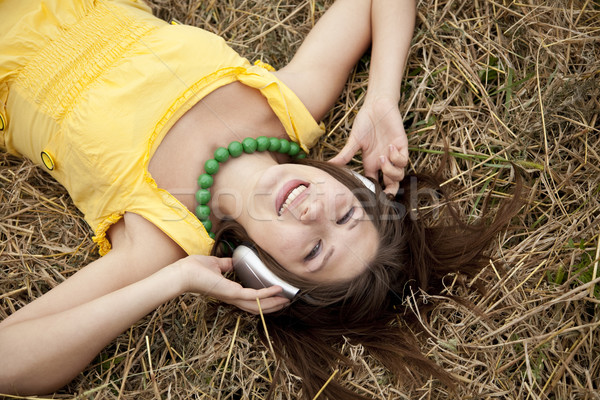 Young beautiful girl in yellow with headphones at field. Stock photo © Massonforstock