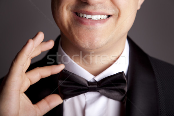 A close-up shot of a man straightening his tux. Stock photo © Massonforstock