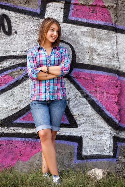 Style teen girl standing near graffiti wall. Stock photo © Massonforstock