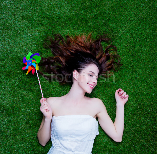 Portrait of a young redhead woman with pinwheel lying down on gr Stock photo © Massonforstock