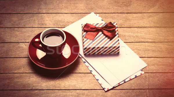 photo of cup of coffee, envelopes and cute wrapped gift on the w Stock photo © Massonforstock