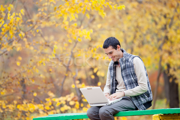 photo of handsome man sitting on the bench with laptop on the wo Stock photo © Massonforstock