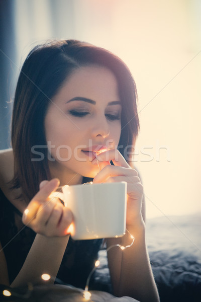 woman with fairy lights and cup of coffee  Stock photo © Massonforstock