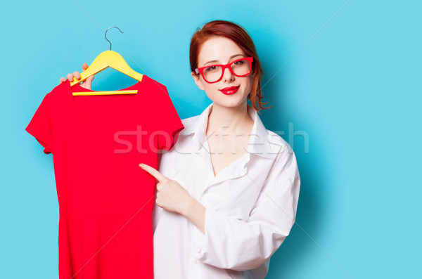photo of beautiful young woman holding shirt on hanger on the wo Stock photo © Massonforstock