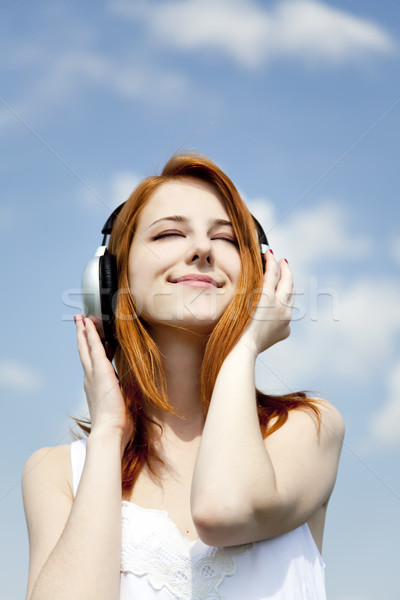 Redhead girl with headphone at sky background. Stock photo © Massonforstock