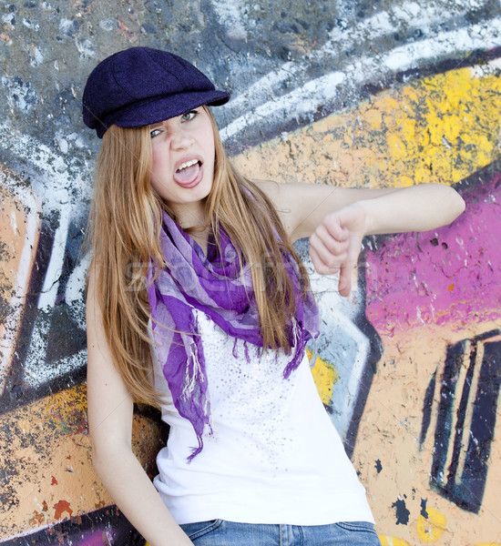 Grimacing teen girl near graffiti wall. Stock photo © Massonforstock