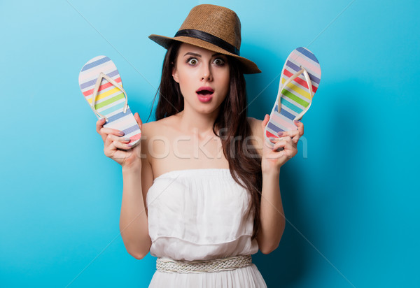 Stock photo: beautiful surprised young woman with sandals standing in front o