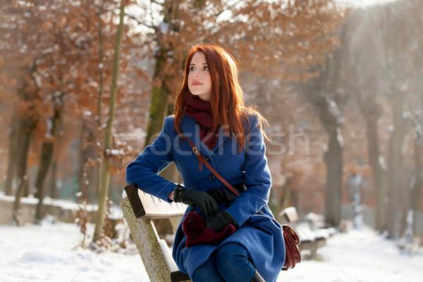 Fotografia piękna młoda kobieta posiedzenia ławce parku Zdjęcia stock © Massonforstock