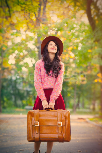 photo of beautiful young woman with suitcase standing in the par Stock photo © Massonforstock