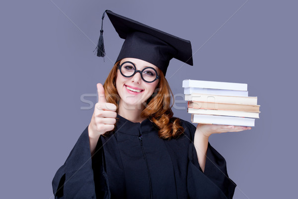photo of beautiful young alumnus with pile of books on the wonde Stock photo © Massonforstock