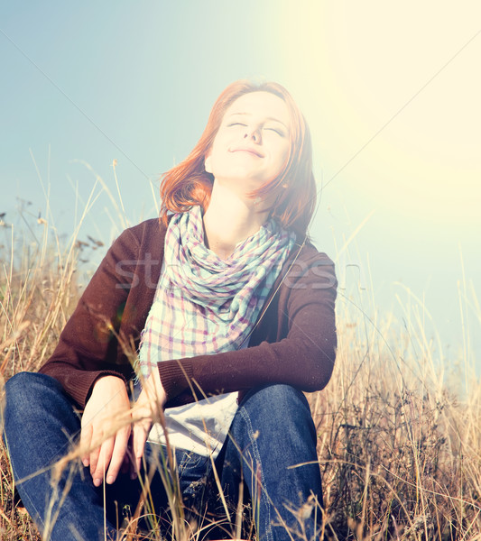 Portrait of happy red-haired girl on autumn grass. Stock photo © Massonforstock