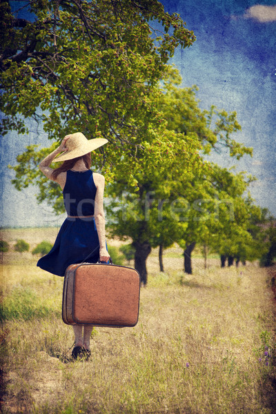 Redhead girl with suitcase at tree's alley. Stock photo © Massonforstock
