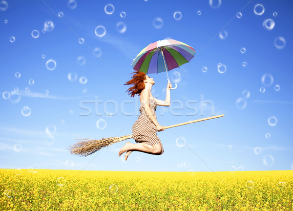 Red-haired girl fly with umbrella over rape field and bubbles ar Stock photo © Massonforstock