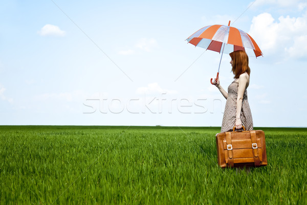 Redhead enchantress with umbrella and suitcase at spring wheat f Stock photo © Massonforstock