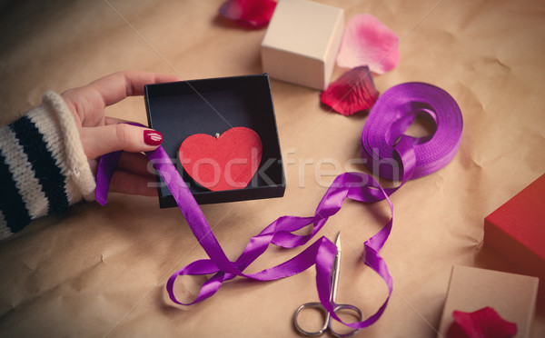 white caucasian hand wrapping heart shaped toy in box on the won Stock photo © Massonforstock