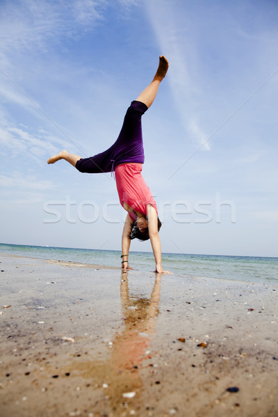 Young girl show an acrobatic on the beach. Stock photo © Massonforstock