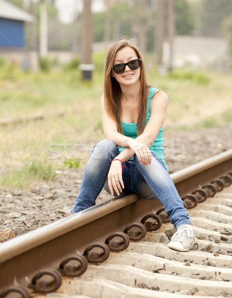 Stock photo: Young girl in glasses sitting at railway.
