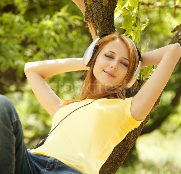 Redhead girl with headphones lie over tree at garden. Stock photo © Massonforstock