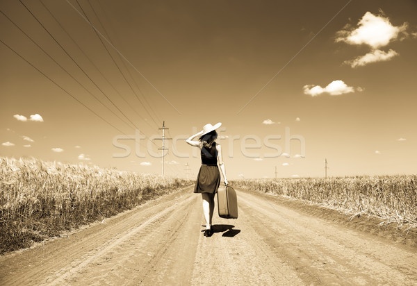 Lonely girl with suitcase at country road Stock photo © Massonforstock