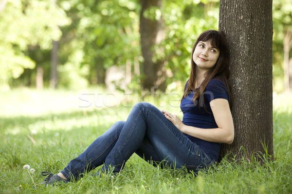 Stock photo: Young fashion girl with headphones at green spring grass.