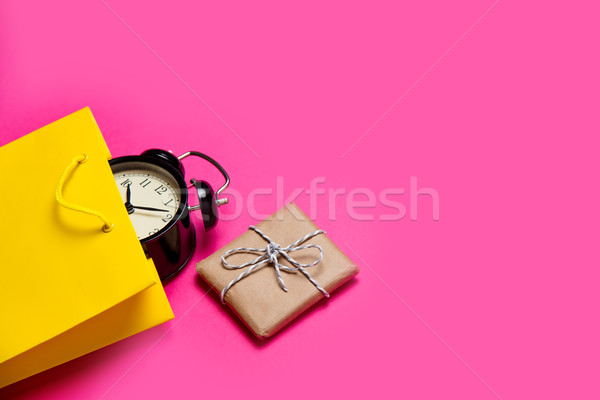 cool black alarm clock in beautiful yellow shopping bag and cute Stock photo © Massonforstock