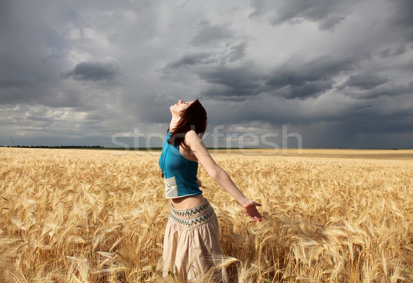 Girl at wheat field in storm day.  Stock photo © Massonforstock