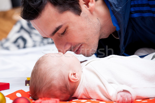 photo of father kissing his sleeping baby near gifts and baubles Stock photo © Massonforstock